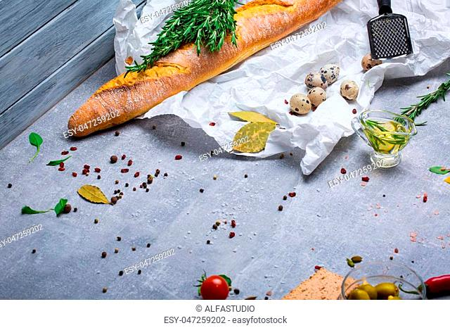 A beautiful colorful composition of lunch ingredients and spices on a gray background. White baguette, quail eggs, bay leaves