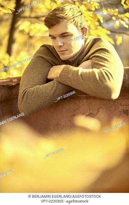 Young thoughtful man outdoors in autumn, thoughtful, reminiscing, in Munich, Germany
