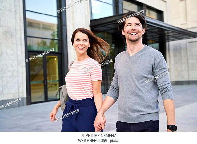 Happy couple walking hand in hand in the city
