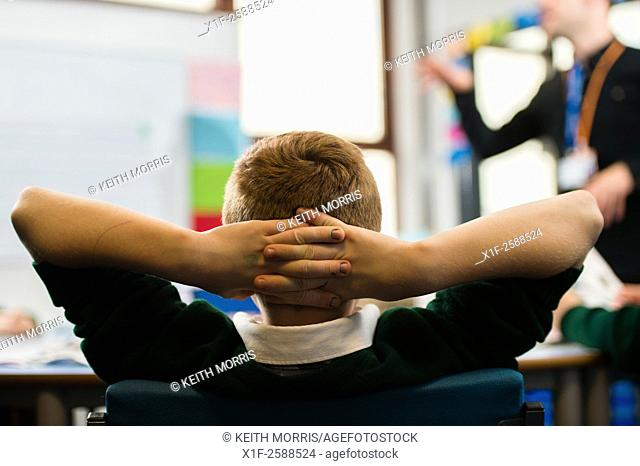 A young teenage boy in a secondary school class classroom lesson , leaning back, hands behind his head, listening to a teacher teaching, UK