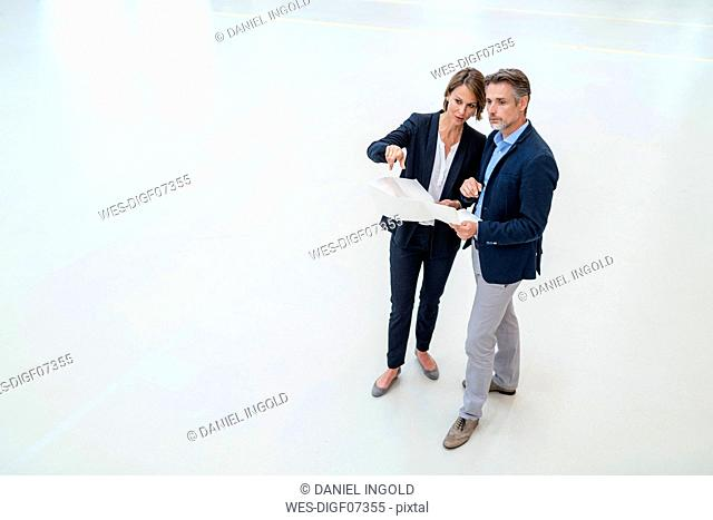 Businessman and businesswoman discussing plan