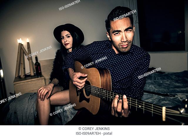 Young couple sitting on bed, young man playing guitar