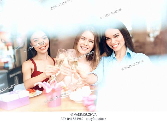 Girls celebrate the holiday on March 8 in a cafe. They are friends. Girls have tulips and gifts. They are cheerful and happy on a women's day