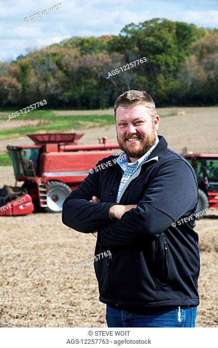 Portrait of a farmer with his farmland and equipment in the background; Minnesota, United States of America