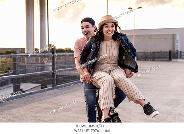 Happy young couple together on a bicycle on parking deck