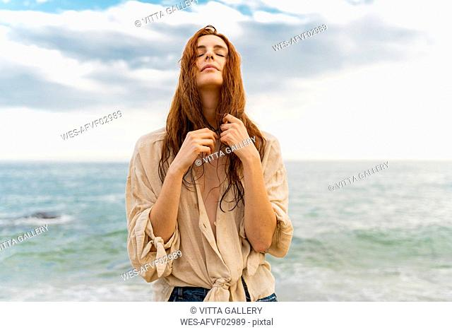 Portrait of redheaded young woman with nose piercing standing in front of the sea