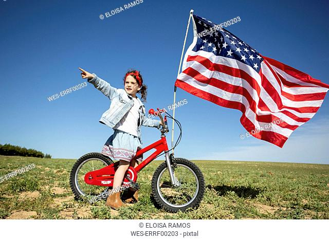 Girl with bicycle and American flag on field in remote landscape