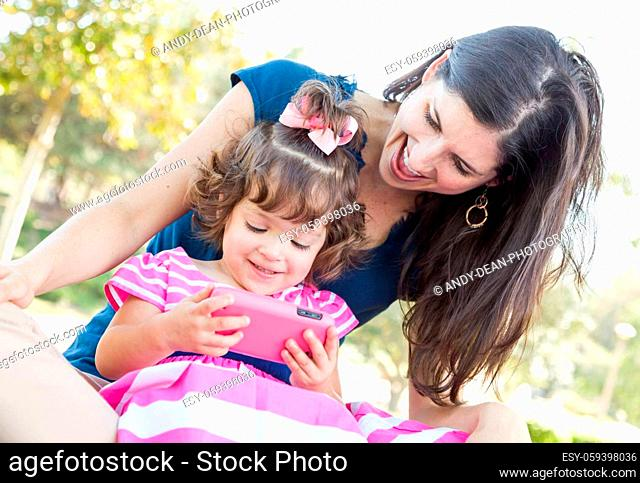 Mixed Race Mother and Cute Baby Daughter Playing with Cell Phone in Park