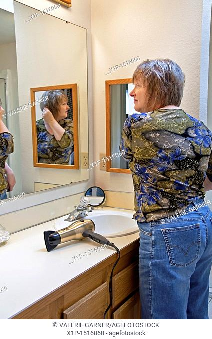This middle aged Caucasian woman is fixing her hair after blow drying it in the bathroom, looking in a mirror  An everday grooming moment lifestyle stock image