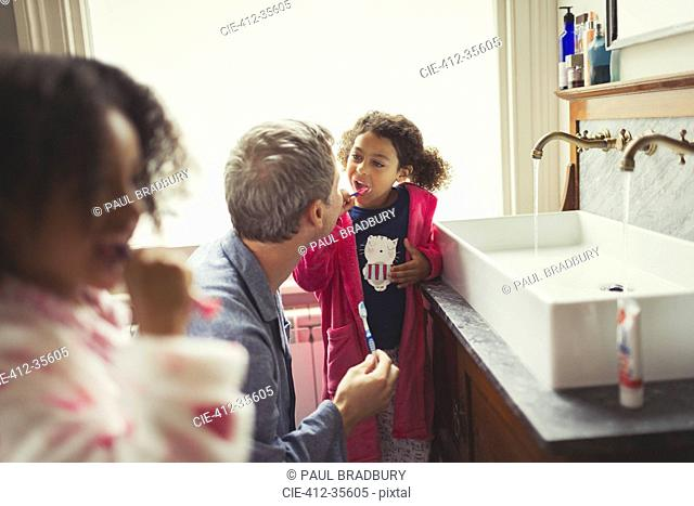 Multi-ethnic father watching daughter brushing teeth at bathroom sink