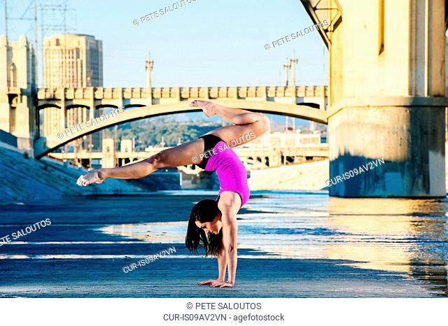 Side view of dancer doing handstand, legs open, Los Angeles, California, USA