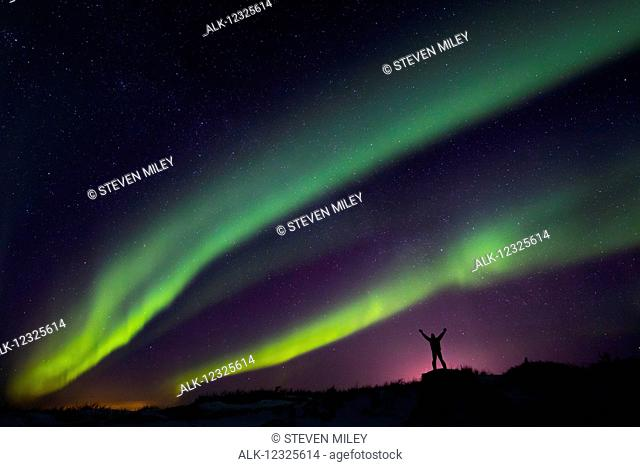 Colourful Aurora borealis over a man with arms outstretched silhouetted against light pollution from nearby Fort Greely; Alaska, United States of America