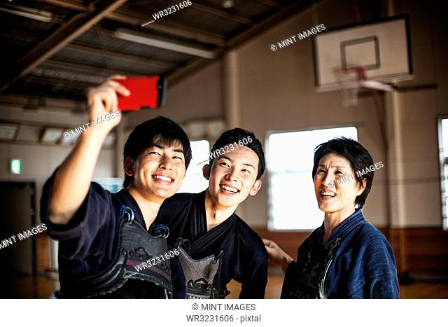 Smiling female and two male Japanese Kendo fighters standing in a gym, taking selfie with mobile phone
