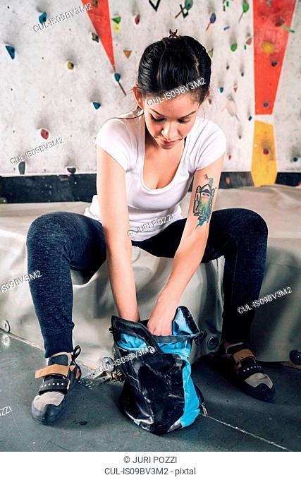 Woman getting climbing chalk from chalk bag