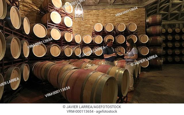 Couple tasting wine in cellar, Barrel cellar, Bodegas Olarra, Logroño, La Rioja, Spain