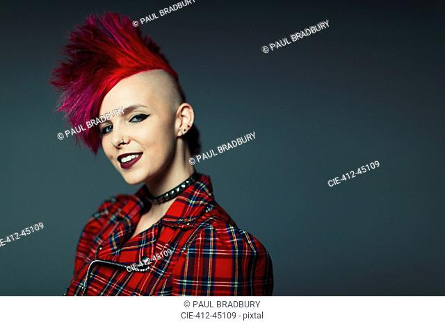 Portrait confident, cool young woman with pink mohawk