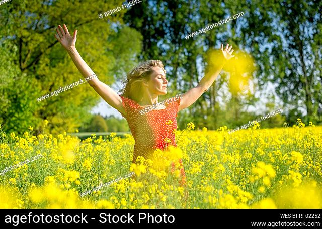 Woman wearing red dress with arms raised standing amidst oilseed rapes