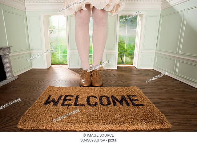 Legs of a woman and welcome mat in small room