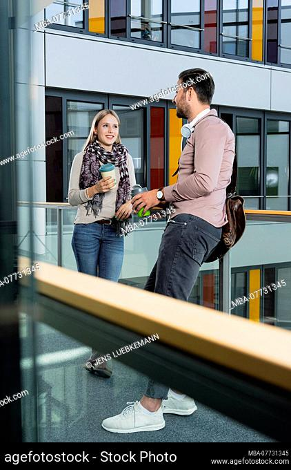 Young woman and young man in modern office building make break