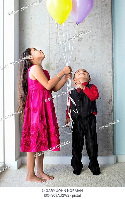 Young girl and boy, holding balloons