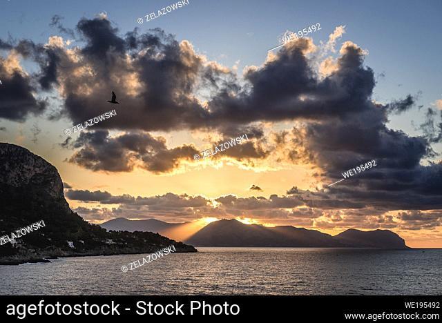 Sunset over Tyrrhenian Sea seen from Zafferano cape near Santa Flavia on Sicily Island in Italy, Gallo cape and Pellegrino mount on background