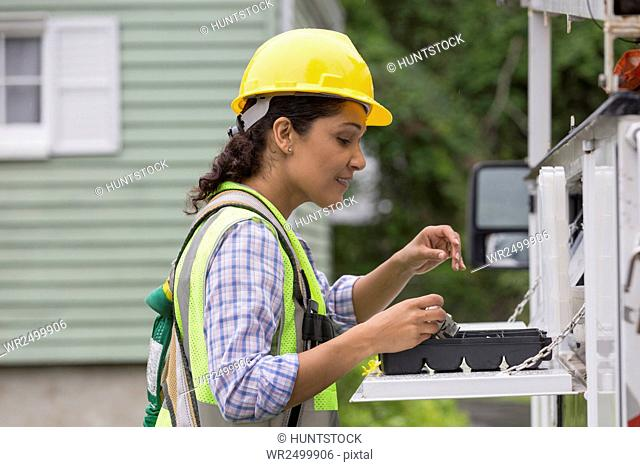 Hispanic female utility worker with tools at site