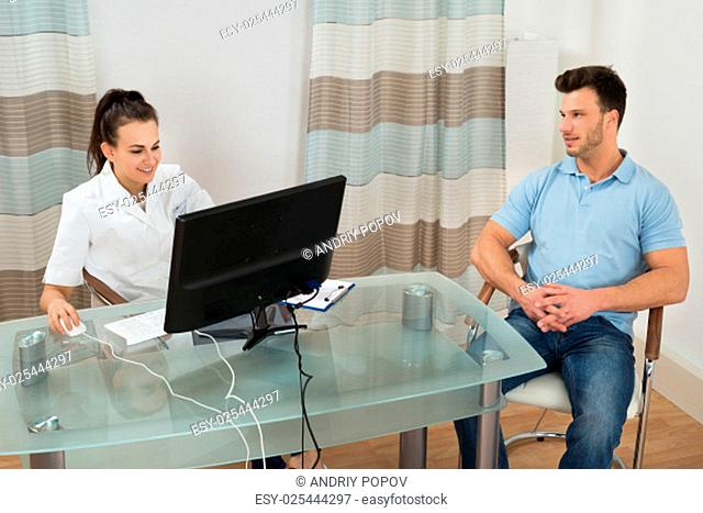 Female Doctor And Patient Sitting In Clinic