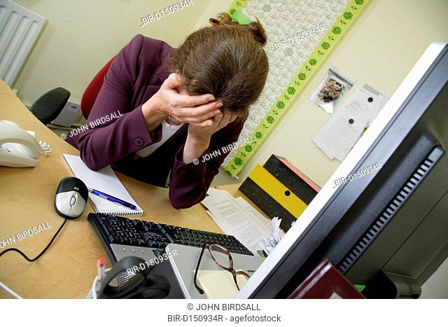 Stressed woman with head in hands at office desk