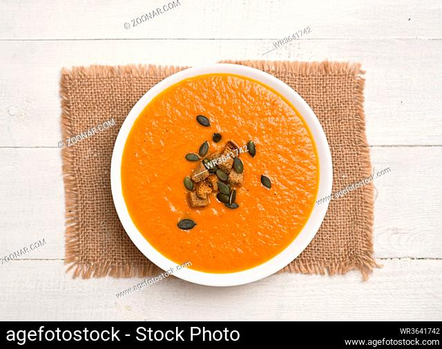 Tomato cream soup with pumpkin seeds and crackers on a wooden background