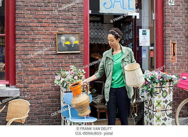 Female customer with jug and lamp outside vintage shop