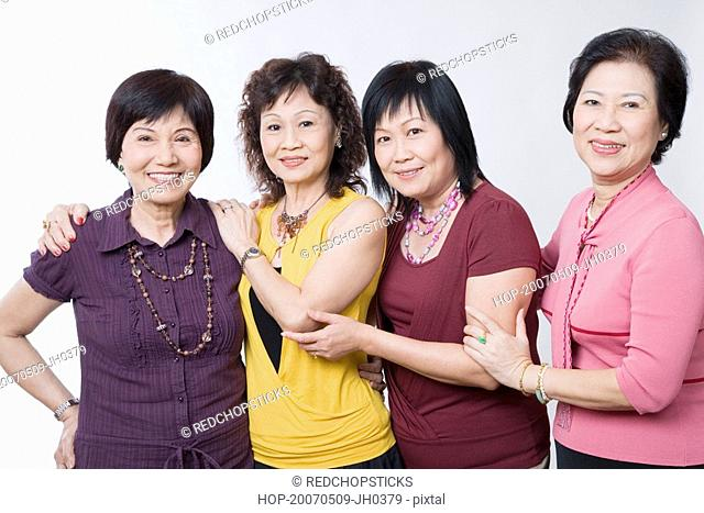 Portrait of three senior women and a mature woman standing together and smiling