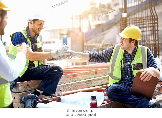 Construction workers and engineer enjoying coffee break at construction site