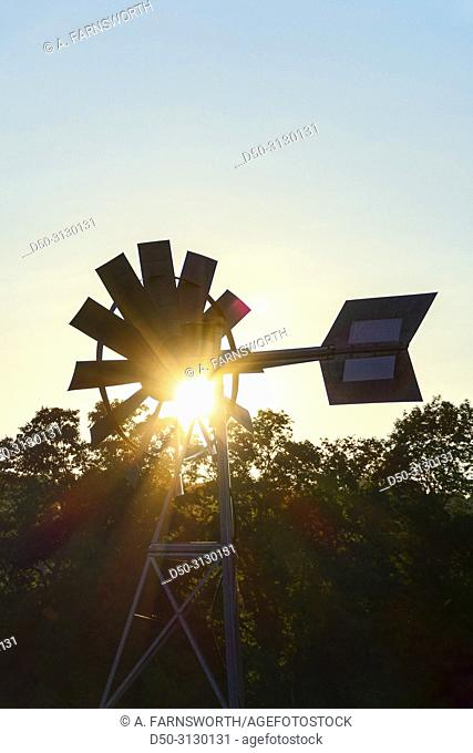 Sharon, Conecticut, USA A windmill and weathervane at a farm at sunset