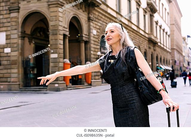 Mature woman with long grey hair with wheeled suitcase hailing a cab in Florence, Italy