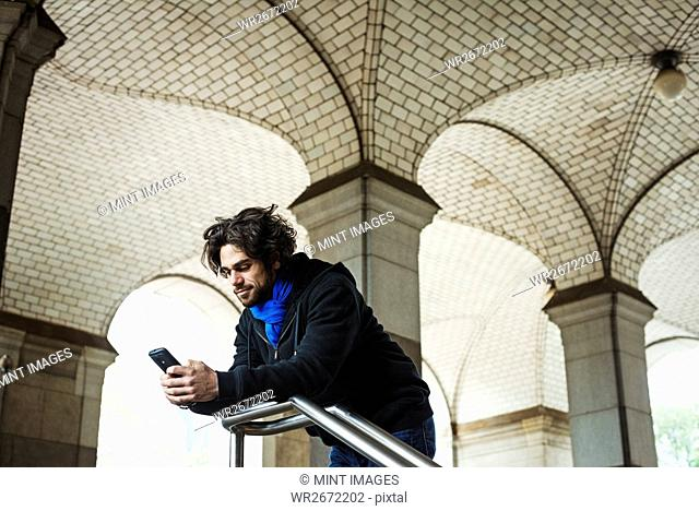 A man checking his smart phone and leaning on a stair railing