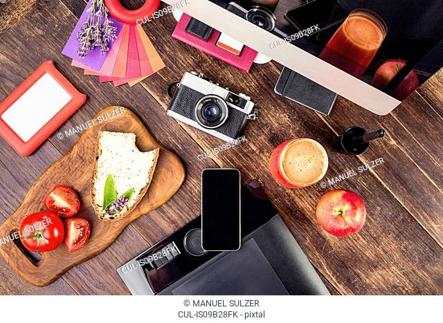 Overhead view of photo editing equipment; graphic tablet, retro camera, smartphone, desktop computer and lunch