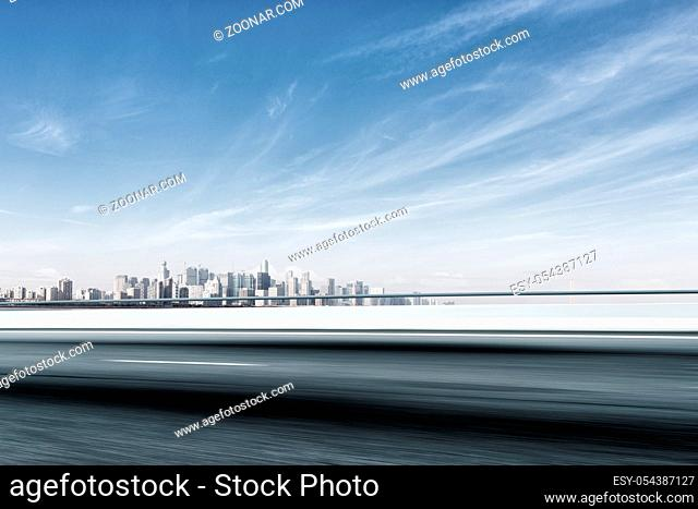 blurred cityscape of hangzhou in blue cloud sky from empty road