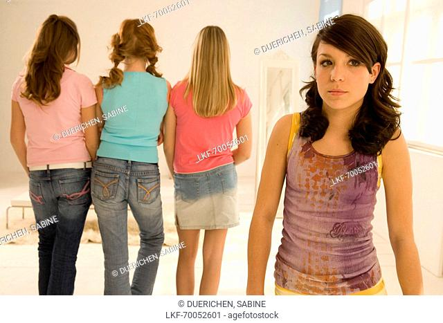 Teenage girl (14-16) standing out from other girls, bullying