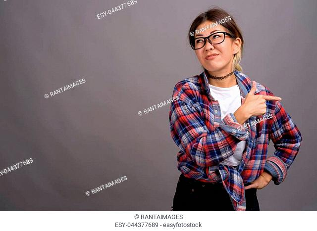 Studio shot of young beautiful Kazakh woman wearing checkered shirt against gray background