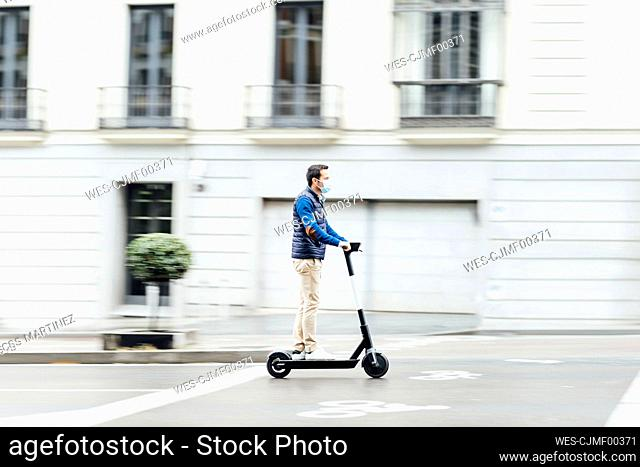 Young man wearing protective face mask riding electric push scooter on street in city