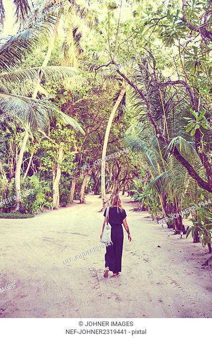 Woman walking under palms