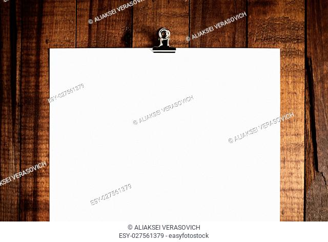 Closeup of blank paper poster hanging on wooden background. For design portfolios. Mock up for branding identity. Front view