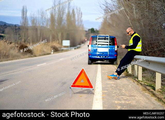 Man using a smartphone having a car breakdown