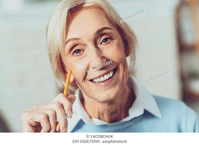 Mature beauty. Happy mature woman showing her smile and holding pencil in right hand