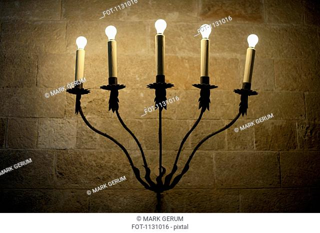 A sconce with illuminated electric candles
