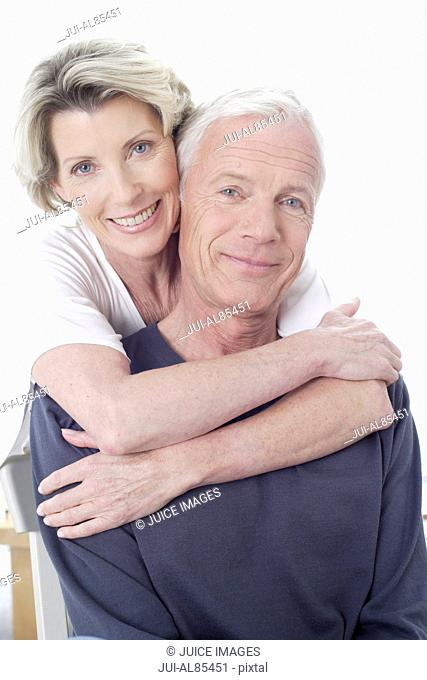 Senior couple smiling and hugging indoors