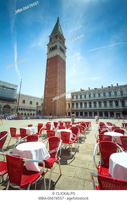 Europe, Italy, Veneto, Venice. The bell tower and the square of St. Mark with the cafe's chairs and tables