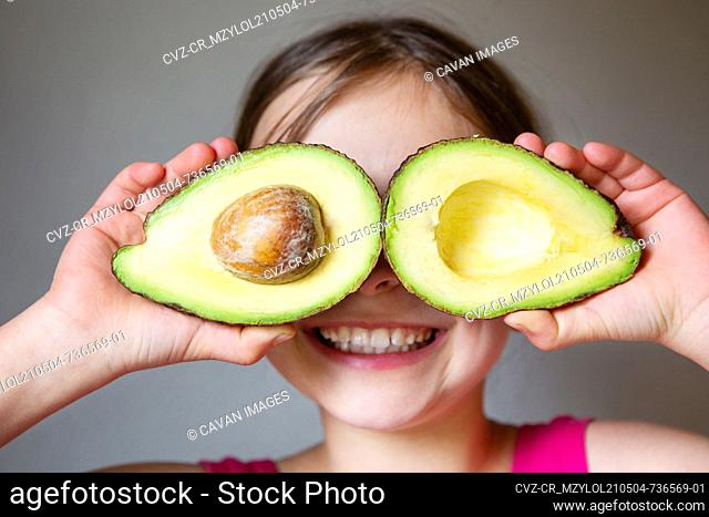 Portrait of young smiling girl with ripe delicious avocado