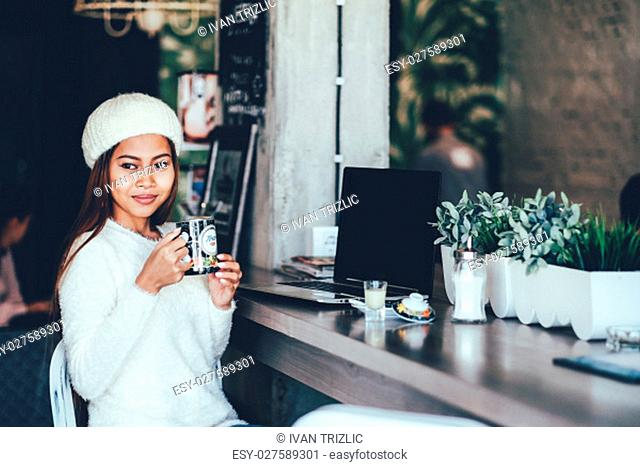Attractive beautiful girl enjoying drinking tea in a cafe with a laptop on table