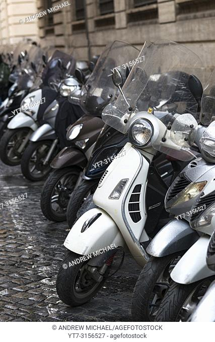 Vespas and other motorcycles on Rome cobbled streets, Lazio, Italy